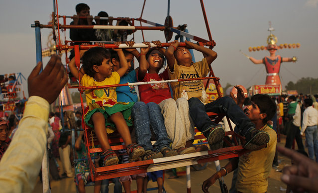 Indian children react as they take a ride at a fairground before the burning of effigies of demon king Ravana, during Dussehra celebrations on the outskirts of New Delhi, India, Friday, October 3, 2014. Dussehra commemorates the triumph of Lord Rama over the demon king Ravana, marking the victory of good over evil. (Photo by Altaf Qadri/AP Photo)