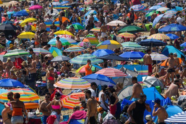 People enjoy the hot weather at the beach in Bournemouth, Britain, June 24, 2020. (Photo by Toby Melville/Reuters)