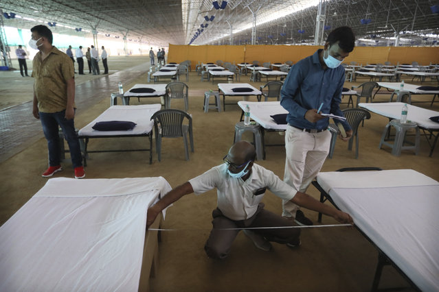 Volunteers measure the space between beds as they prepare a facility that can accommodate more than ten thousand COVID-19 patients at the Radha Soami Satsang Beas complex, one of the biggest in India, in the Chattarpur area of New Delhi, India, Wednesday, June 24, 2020. New Delhi, which is among India's worst hit three states is emerging a cause of concern for the federal government and is being criticized for its poor contact tracing and a lack of enough hospital beds as India is the fourth hardest-hit country by the pandemic in the world after the U.S., Russia and Brazil. (Photo by Manish Swarup/AP Photo)