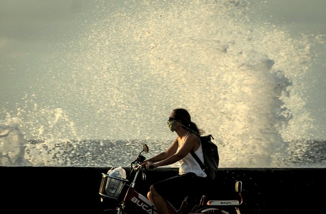 A woman wearing a mask as a precaution against the spread of the new coronavirus drives an electric bicycle while a wave crashes into the sea wall in Havana, Cuba, Tuesday, May 12, 2020. Cuban authorities are requiring the use of masks for anyone outside their homes. (Photo by Ramon Espinosa/AP Photo)