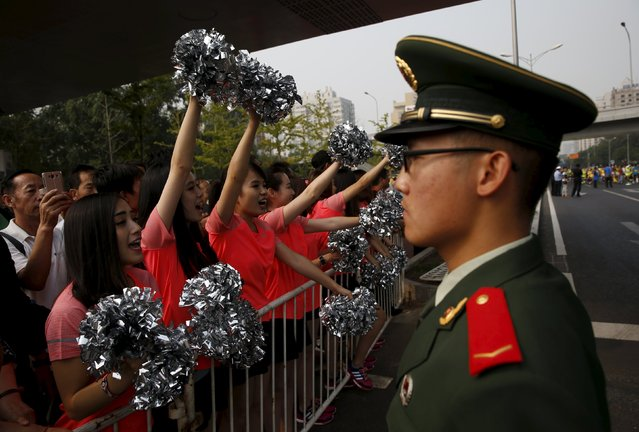 Women cheer at the runners as a paramilitary policeman stands guard during the Beijing International Marathon in Beijing, China, September 20, 2015. (Photo by Kim Kyung-Hoon/Reuters)