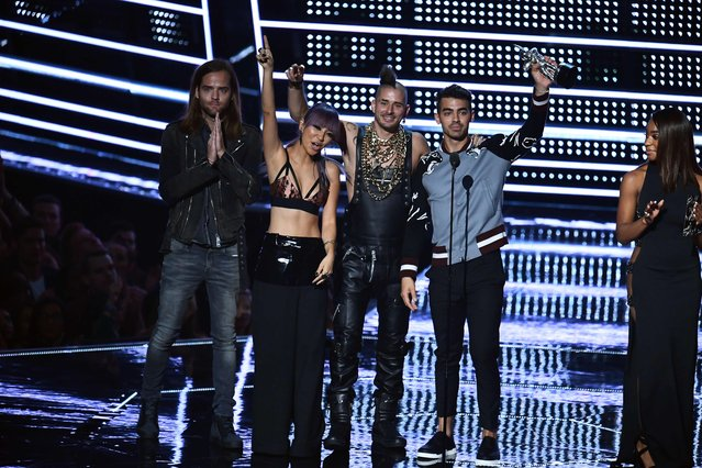 (L-R) Jack Lawless, JinJoo Lee, Cole Whittle, and Joe Jonas of DNCE accept an award on stage during the 2016 MTV Video Music Award at the Madison Square Garden in New York on August 28, 2016. (Photo by Jewel Samad/AFP Photo)