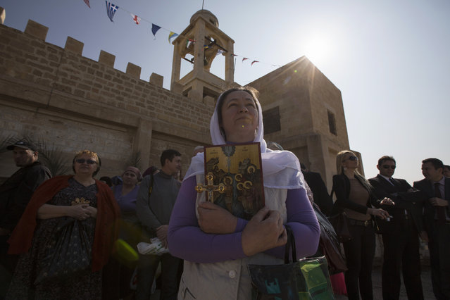 A Christian pilgrim holds a cross before a ceremony at the baptismal site known as Qasr el-Yahud on the banks of the Jordan River near the West Bank city of Jericho January 18, 2014. (Photo by Baz Ratner/Reuters)