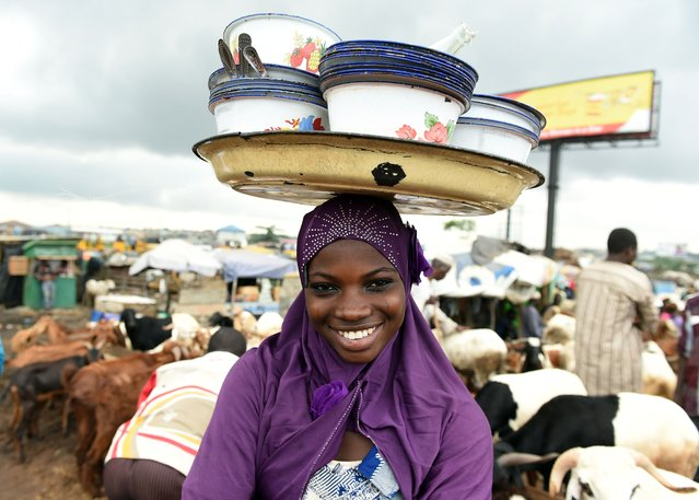 A young vendor hawks food on a market in Kara in the state of Ogun, on September 23, 2015. Nigeria imposed tight movement restrictions in the restive northeast after Boko Haram bombings that killed more than 100 raised fears of fresh attacks over the Eid al-Adha festival. The military said the use of all vehicles would be banned throughout Borno state during the Muslim festival, which is known as Sallah in Nigeria and marked with two days' public holiday from Thursday. (Photo by Pius Utomi Ekpei/AFP Photo)