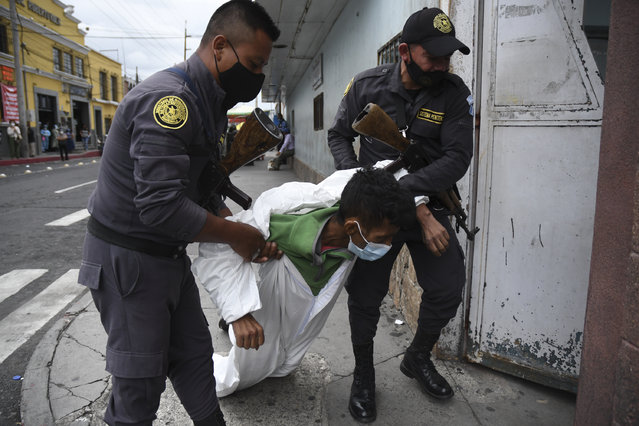 Penitentiary system guards carry an inmate with symptoms related to the novel coronavirus at the COVID-19 unit of San Juan de Dios hospital in Guatemala City on July 13, 2020. (Photo by Johan Ordonez/AFP Photo)