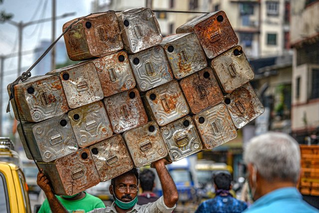 A labourer carries a load of empty oil tins in Dharavi in Mumbai on July 23, 2020. (Photo by Indranil Mukherjee/AFP Photo)