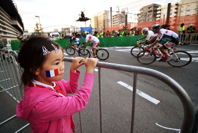 A Japanese girl with a French flag face painting watches the race of the Saitama Criterium in Saitama, suburban Tokyo on October 25, 2014. German Marcel Kittel of Giant-Shimano won. (Photo by Yoshikazu Tsuno/AFP Photo)