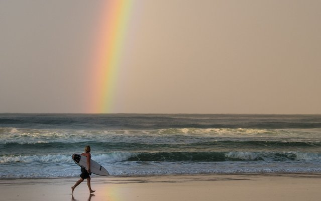 A surfer on Coolangatta beach, Queensland, Australia with a rainbow in the background on December 5, 2017. (Photo by James Gourley/Rex Features/Shutterstock)