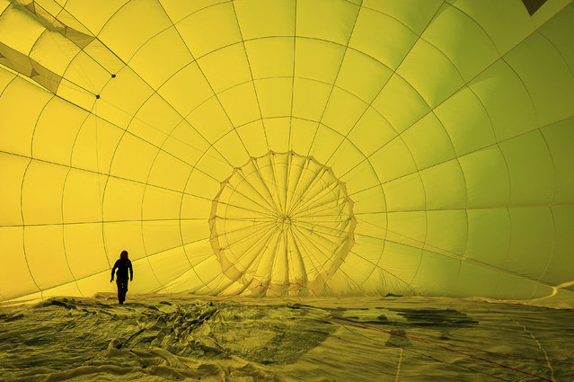 A hot air balloon pilot checks her rigging inside the canopy before a mass ascent, with 43 balloon teams taking part, for a Fiesta Flypast over the city of Bristol as part of the socially distanced alternative to the Bristol International Balloon Fiesta on Monday August 3, 2020. (Photo by Ben Birchall/PA Wire via AP Photo)