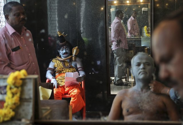 An Indian actor dressed as Hindu god Shiva, sitting left, memorizes the scripted lines as another gets his make up done before performing in a play based on Hindu mythology at a theater in  Bangalore, India, Thursday, October 30, 2014. (Photo by Aijaz Rahi/AP Photo)