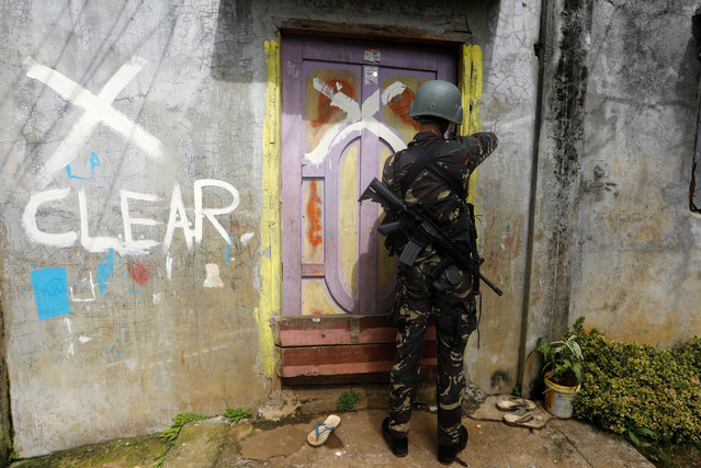 A member of the Philippine National Police closes a door after marking a house as clear while government troops continue their assault against insurgents from the Maute group in Marawi city, June 29, 2017. (Photo by Jorge Silva/Reuters)
