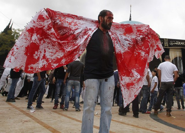 A Shi'ite Muslim man displays a cloth covered in his blood after tapping his forehead with a razor during a Muharram procession to mark Ashoura in Nabatieh town, southern Lebanon November 4, 2014. (Photo by Ali Hashisho/Reuters)