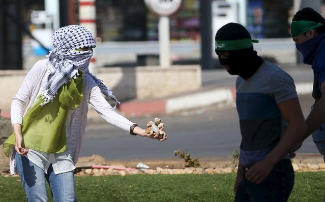 A Palestinian girl gives stones to protesters during clashes with Israeli troops near the Jewish settlement of Bet El, near the West Bank city of Ramallah October 8, 2015. (Photo by Mohamad Torokman/Reuters)