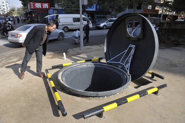 A resident looks into a newly-built giant trash can, partially buried underground, next to a street in Taiyuan, Shanxi province November 6, 2014. The trash can, which has a diameter of 1.9 meters and a depth of 2.8 meters, could contain approximately 10 cubic metres of garbage. It was built to replace an open-air garbage dump site, local media reported. (Photo by Reuters/Stringer)