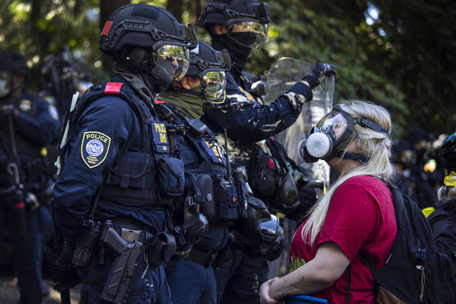 A protester, wearing a gas mask, confronts members of the Portland police during clashes between the Alt-Right Proud Boy group and Black Lives Matter protesters in Portland, Oregon on August 22, 2020. For the second Saturday in a row, right wing groups gathered in downtown Portland, sparking counter protests and violence. (Photo by Paula Bronstein/Getty Images)