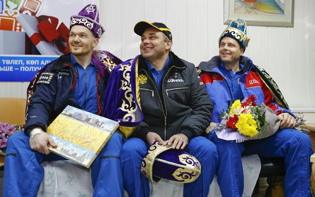 International Space Station (ISS) crew members Alexander Gerst of Germany (L), Maxim Suraev of Russia (C) and Reid Wiseman of the U.S. are presented with the Kazakh national costume during a news conference in Kostanay, northern Kazakhstan November 10,  2014. (Photo by Shamil Zhumatov/Reuters)
