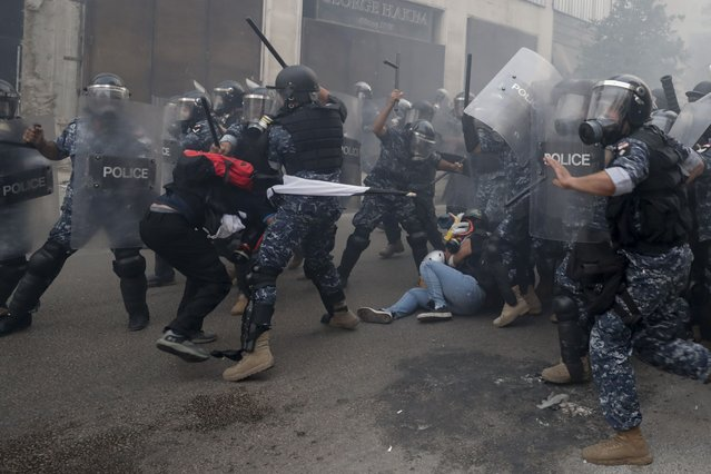 Riot policemen beat anti-government protesters during a protest near Parliament Square, in Beirut, Lebanon, Tuesday, September 1, 2020. On a visit to Lebanon, French President Emmanuel Macron issued a stern warning to Lebanon's political class Tuesday, urging them to commit to serious reforms within a few months or risk punitive action, including sanctions, if they fail to deliver. (Photo by Hassan Ammar/AP Photo)