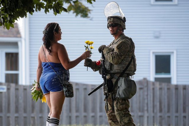 A woman hands flowers to a member of the Wisconsin National Guard standing by as people gather for a vigil, following the police shooting of Jacob Blake, a Black man, in Kenosha, Wisconsin, U.S., August 28, 2020. (Photo by Brendan McDermid/Reuters)
