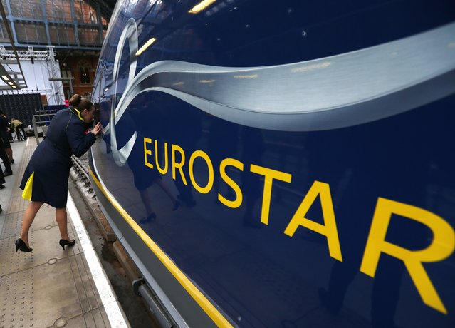 A Eurostar employee peers into the driver's cab of their new Siemens e320 train at St Pancras station in central London, November 13, 2014. (Photo by Andrew Winning/Reuters)