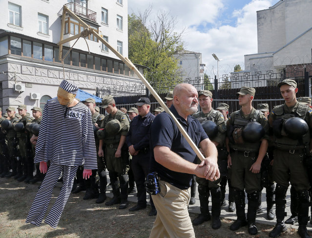 An activist holds a mock figure of Putin during a protest in front of the Russian Embassy, as Ukrainian servicemen and policemen stand guard in Kiev, Ukraine, Sunday, September18, 2016. A group of Ukrainian activists gathered in front of the Russian Embassy to protest against the Russian parliamentary elections in a polling station on the territory of the Russian Embassy. Russia's weekend parliament elections take place under new rules that in principle could bring genuine opposition into the national legislature. (Photo by Efrem Lukatsky/AP Photo)