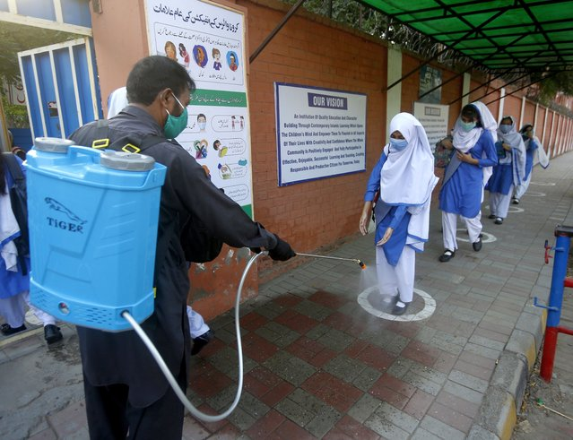 A worker disinfects shoes of a student upon her arrival at a school, in Lahore, Pakistan, Tuesday, September 15, 2020. Pakistani officials welcomed millions of children back to school following educational institutions reopened on Tuesday in the country amid a steady decline in coronavirus deaths and infections. (Photo by K.M. Chaudary/AP Photo)