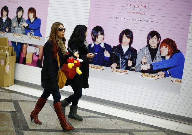 Women walk past an advertising billboard in the Dotonbori amusement district of Osaka, western Japan, November 19, 2014. (Photo by Thomas Peter/Reuters)