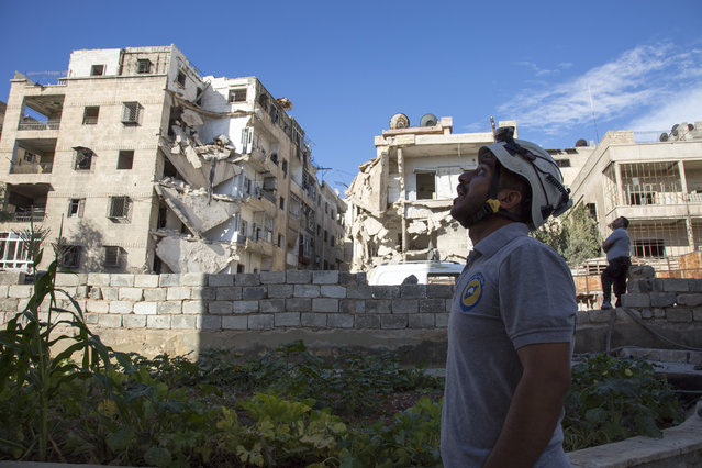 A Syrian rescuer looks towards the sky following an air strike in the rebel-held Ansari district in the northern Syrian city of Aleppo on September 23, 2016. Syrian and Russian aircraft pounded rebel-held areas of Aleppo, a monitor said, after the army announced a new offensive aimed at retaking all of the divided second city. An AFP correspondent in the opposition-held east of the city reported relentless bombardment with air strikes, barrel bombs and artillery fire hitting multiple neighbourhoods. (Photo by Karam Al-Masri/AFP Photo)