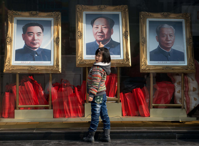 A girl stands before portraits of former Chinese leaders (L – R) Zhou Enlai, Mao Zedong and Liu Shaoqi in Beijing on February 26, 2013. On March 5 China will convene a key legislative session, state media reported, with new Communist Party chief Xi Jingping set to become president during the two-week meeting. (Photo by Ed Jones/AFP Photo)