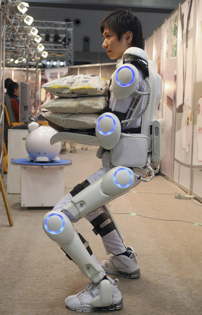 "Robot suit ""Hybrid Assistive Limb (HAL)"" worn by a man developed by University of Tsukuba is seen lifting a 30kg weight during 2005 International Robot Exhibition on November 30, 2005 in Tokyo, Japan. By wearing the power suit, it makes it easier to move and lift heavy things. The Exhibition is on until December 3. (Photo by Koichi Kamoshida)"