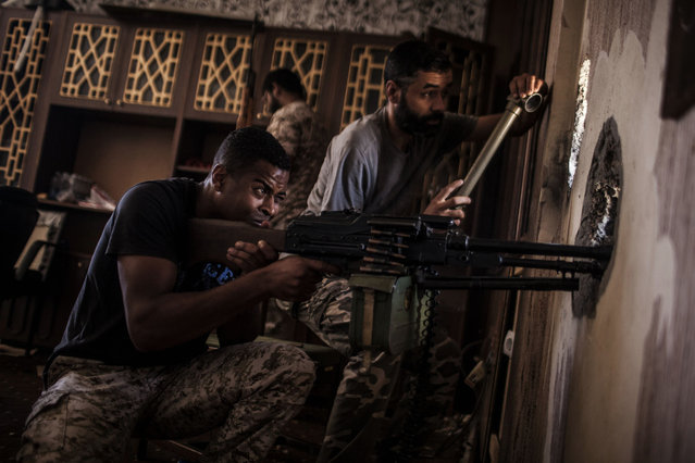 A fighter of the Libyan forces affiliated to the Tripoli government searches for sniper positions, from a building, on the front line in Sirte, Libya, Tuesday, September  27, 2016. (Photo by Manu Brabo/AP Photo)