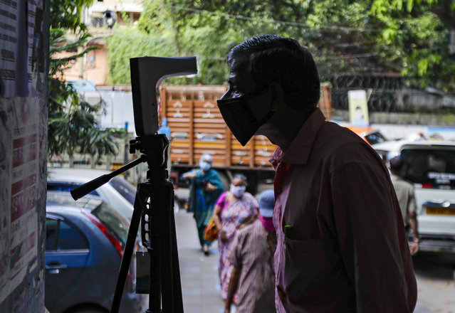 A man checks his body temparature on a device installed at the entrance of a government office, set up as a precautionary measure to check the spread of the coronavirus in Kolkata, India, Tuesday, October 13, 2020. India has registered 55,342 new confirmed coronaviruses cases in the past 24 hours, the lowest since mid-August. The Health Ministry raised India's confirmed total to more than 7.17 million on Tuesday but said the country was showing a trend of declining average daily cases over the last five weeks. (Photo by Bikas Das/AP Photo)