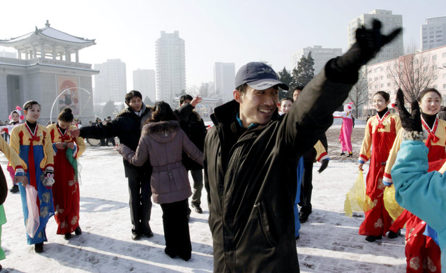 In this Wednesday, December 12, 2012 file photo, North Korean youths dance before the Pyongyang Grand Theatre in Pyongyang, North Korea, to celebrate a rocket launch after North Korea successfully fired a long-range rocket. (Photo by Jon Chol Jin/AP Photo)