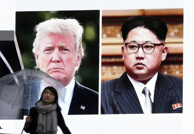 A woman walks by a huge screen showing U.S. President Donald Trump, left, and North Korea's leader Kim Jong Un, in Tokyo, Friday, March 9, 2018. After a year of threats and diatribes, U.S. President Donald Trump and third-generation North Korean dictator Kim Jong Un have agreed to meet face-to-face for talks about the North's nuclear program. (Photo by Koji Sasahara/AP Photo)