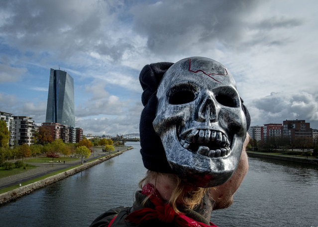 A young man wears a mask on the right side of his head as he stands on a bridge with the European Central Bank at left in Frankfurt, Germany, Thursday, October 29, 2020. (Photo by Michael Probst/AP Photo)