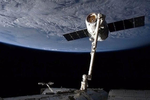 SpaceX's Dragon cargo capsule is snared by the International Space Station's robotic arm in preparation for its berthing on March 3, 2013. The unmanned capsule delivered hundreds of pounds of supplies, and brought more than a ton of cargo back to Earth on March 26. (Photo by Chris Hadfield/CSA via AFP Photo)