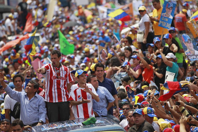 Venezuela's opposition leader and presidential candidate Henrique Capriles (2nd L) greets supporters during a campaign rally in the state of Merida April 10, 2013. Capriles denied on Wednesday accusations from acting President Nicolas Maduro that he would scrap popular welfare policies if he wins Sunday's election. (Photo by Carlos Garcia Rawlins/Reuters)