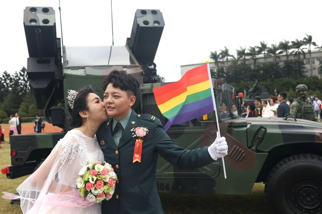 Chen Ying-Hsuan, a combat engineer lieutenant, and her wife Li Chen-Chen, take a photo in front of a AN/TWQ-1 Avenger mobile air defense system at a military mass wedding in Taoyuan, Taiwan, October 30, 2020. Chen and another woman became the first two military officers to marry their same-s*x civilian partners at a mass military wedding in Taiwan, marking another landmark for LGBTQ+ rights in Asia. (Photo by Ann Wang/Reuters)