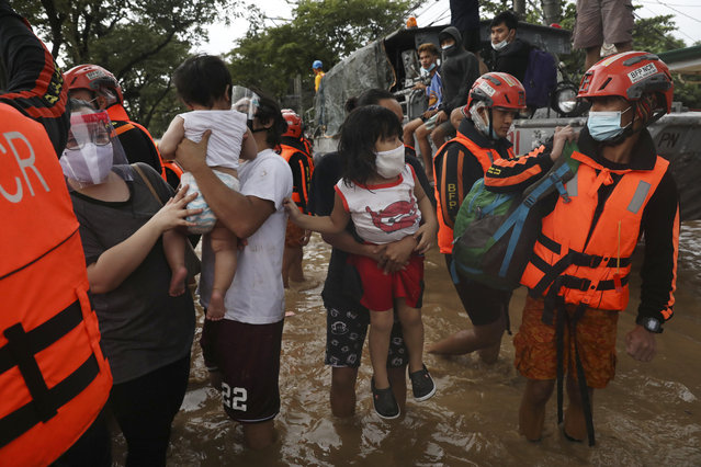 Rescuers assist trapped residents during a rescue operation in Providence village in Marikina City, east of Manila, Philippines, Thursday. November 12, 2020. (Photo by Basilio Sepe/AP Photo)