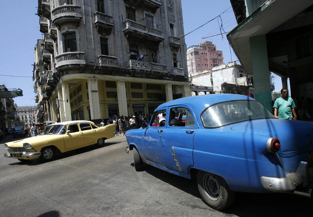 Vintage cars used as cabs drive through Havana, April 26, 2008. (Photo by Claudia Daut/Reuters)
