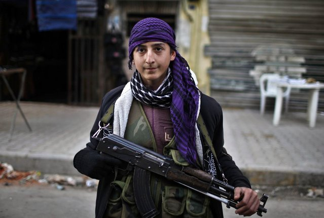 """A boy, a member of the Free Syrian Army, poses with his weapon in Aleppo city December 29, 2012. Syria faces """"hell"""" if no deal is struck to end 21 months of bloodshed, an international mediator said on Saturday, but his talks in Russia brought no sign of a breakthrough after a week of intense diplomacy. (Photo by Ahmed Jadallah/Reuters)"""