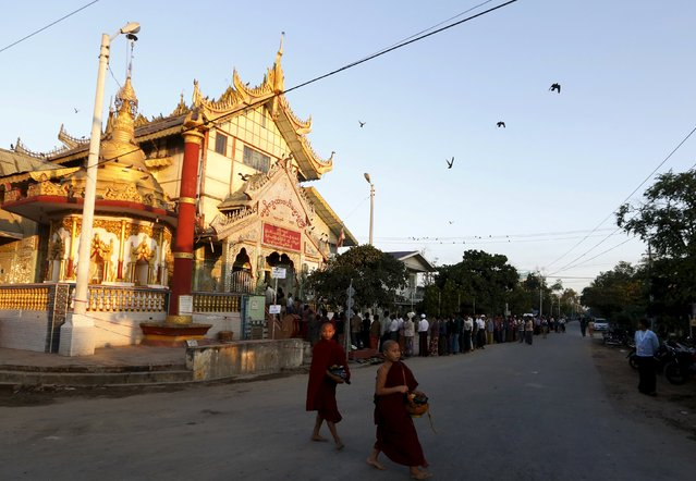 Monks walk past a Buddhist prayer hall as people queue to vote during the general election in Mandalay, Myanmar, November 8, 2015. (Photo by Olivia Harris/Reuters)