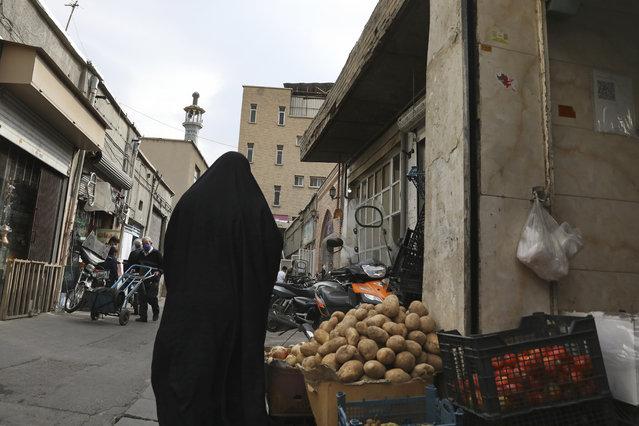 A woman walks in a market street, in Tehran, Iran, Sunday, November 8, 2020. (Photo by Vahid Salemi/AP Photo)