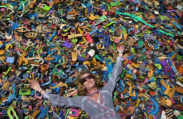 In this photo taken Monday, April 29, 2013, company owner and marine conservationist Julie Church poses for a photograph on a pile of pieces of discarded flip-flops used in a children's play area at the Ocean Sole flip-flop recycling company in Nairobi, Kenya. The company is cleaning the East African country's beaches of used, washed-up flip-flops and the dirty pieces of rubber that were once cruising the Indian Ocean's currents are now being turned into colorful handmade giraffes, elephants and other toy animals. (Photo by Ben Curtis/AP Photo)