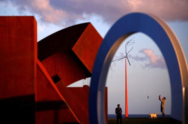 """A member of the public takes a photograph of a sculpture that is part of the annual outdoor exhibition known as """"Sculpture by the Sea"""" near Bondi Beach in Sydney, Australia October 19, 2016 which showcases sculptures by local and international artists along the coastline between Bondi and Tamarama beaches. (Photo by David Gray/Reuters)"""