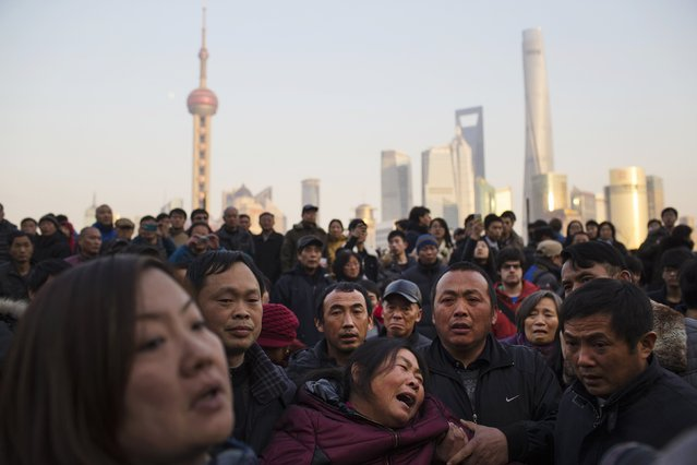A mother (C) of a victim cries at the location where people were killed in a stampede incident during a New Year's celebration on the Bund in Shanghai January 2, 2015. The stampede killed at least 36 people, authorities said, but police denied reports it was caused by people rushing to pick up fake money thrown from a building overlooking the city's famous waterfront. (Photo by Aly Song/Reuters)