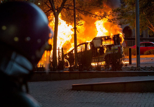 A riot policeman watches as a police vehicle burns in Braamfontein, Johannesburg, South Africa, Tuesday, October 25, 2016. Rioters in South Africa set a police vehicle on fire Tuesday and stoned vehicles near a Johannesburg university that has been the scene of sometimes violent protests by students demanding free education. The violence broke out in streets near the University of the Witwatersrand at around the same time that student protesters met and marched off the campus, South African media reported. (Photo by Yeshiel Panchia/AP Photo)