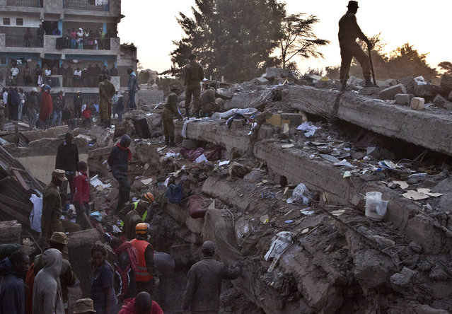 Rescue workers look for survivors at the site of the collapsed building in the capital Nairobi, Kenya , Monday, January 5, 2015. (Photo by Sayyid Azim/AP Photo)