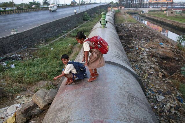 Children get down from a water pipeline used as a path on the way to school in Mumbai January 5, 2015. (Photo by Danish Siddiqui/Reuters)