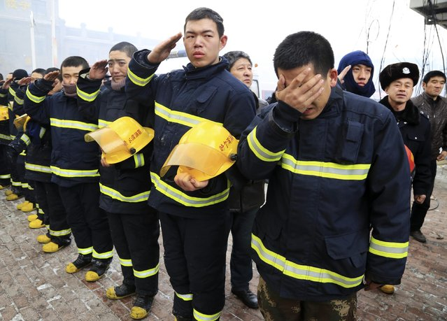 Firefighters salute and cry as they mourn for fellow firefighters, who were killed after a building collapsed during a fire, in Harbin, Heilongjiang province January 3, 2015. Five firefighters were killed and 14 others, mostly firefighters, injured as a ceramics market warehouse, which was part of a 11-storey residential building, collapsed due to a fire. (Photo by Reuters/China Daily)