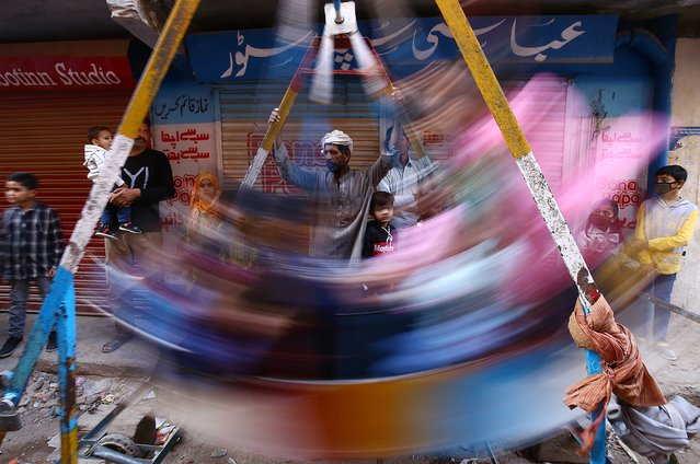 Pakistani Christians children ride a swing during Christmas celebrations in Karachi, Pakistan, 25 December 2020. Pakistan is a Sunni Muslim-majority country, with four million Christians out of a total population of around 200 million residents. (Photo by Shahzaib Akber/EPA/EFE)